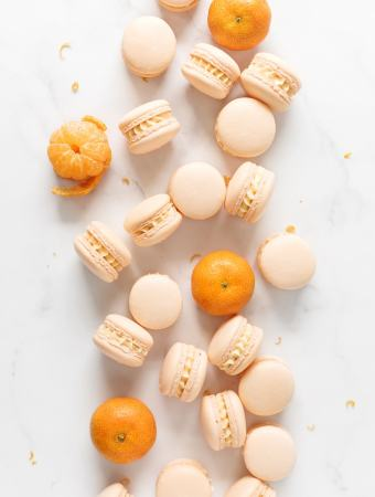 Mandarin orange macarons scattered on marble counter