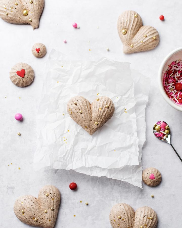 Heart-shaped chocolate meringues on parchment paper with a bowl of pink and red sprinkles