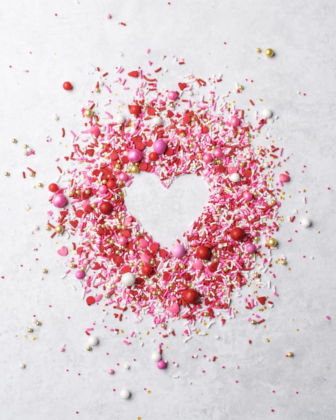 Pink, red, gold, and white sprinkles surrounding a negative space of a heart shape