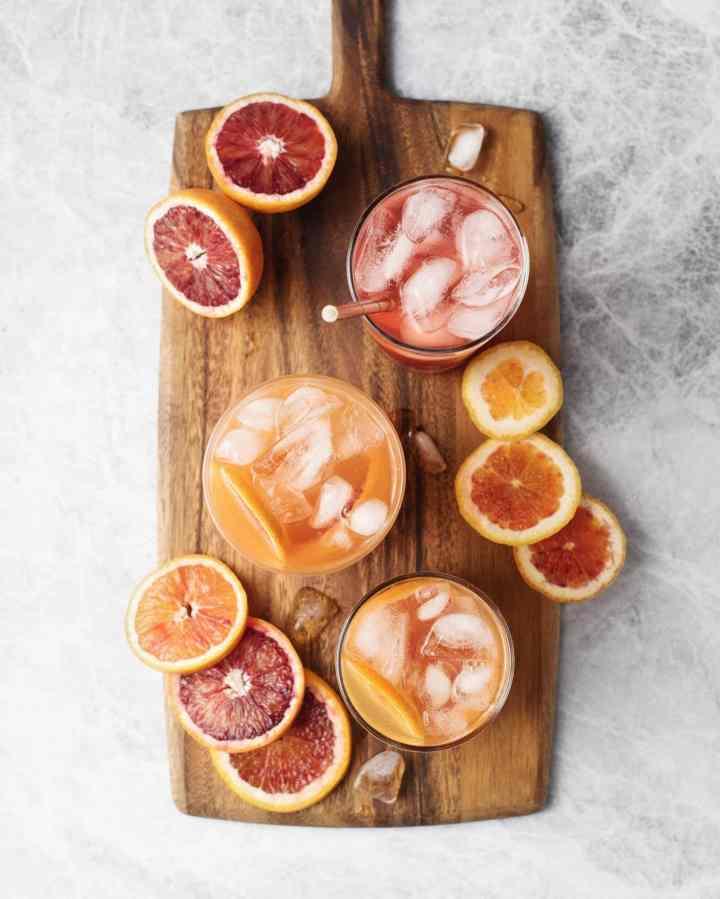 Glasses of blood orange palomas and blood orange slices on a wooden serving board