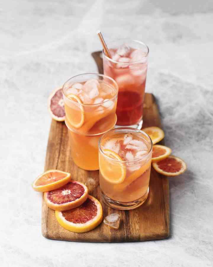 Glasses of blood orange palomas on a wooden serving board