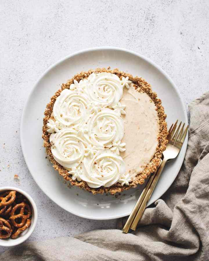 Peanut butter ice cream pie with whipped cream rosettes and brown linen and bowl of pretzels