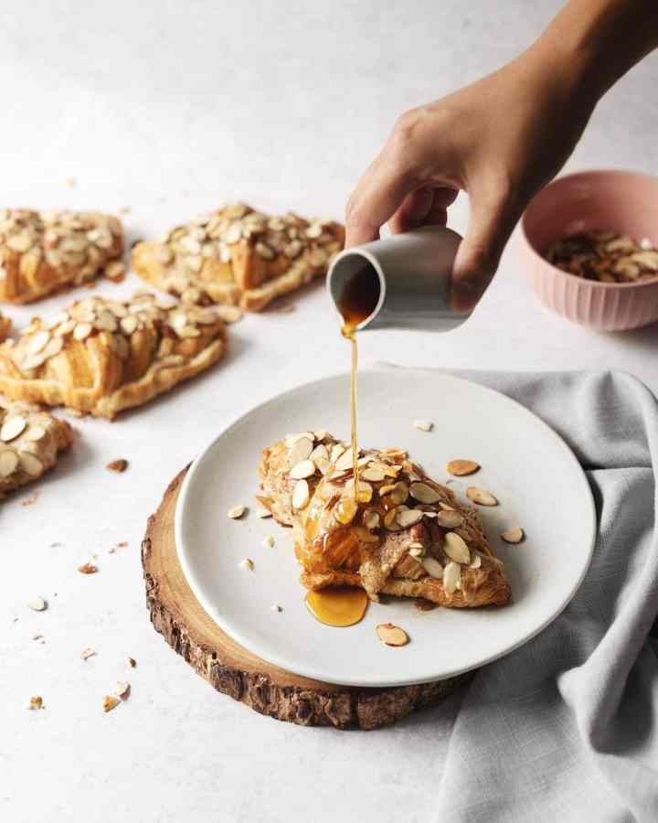 Hand pouring earl grey simple syrup on top of an almond croissant on a plate