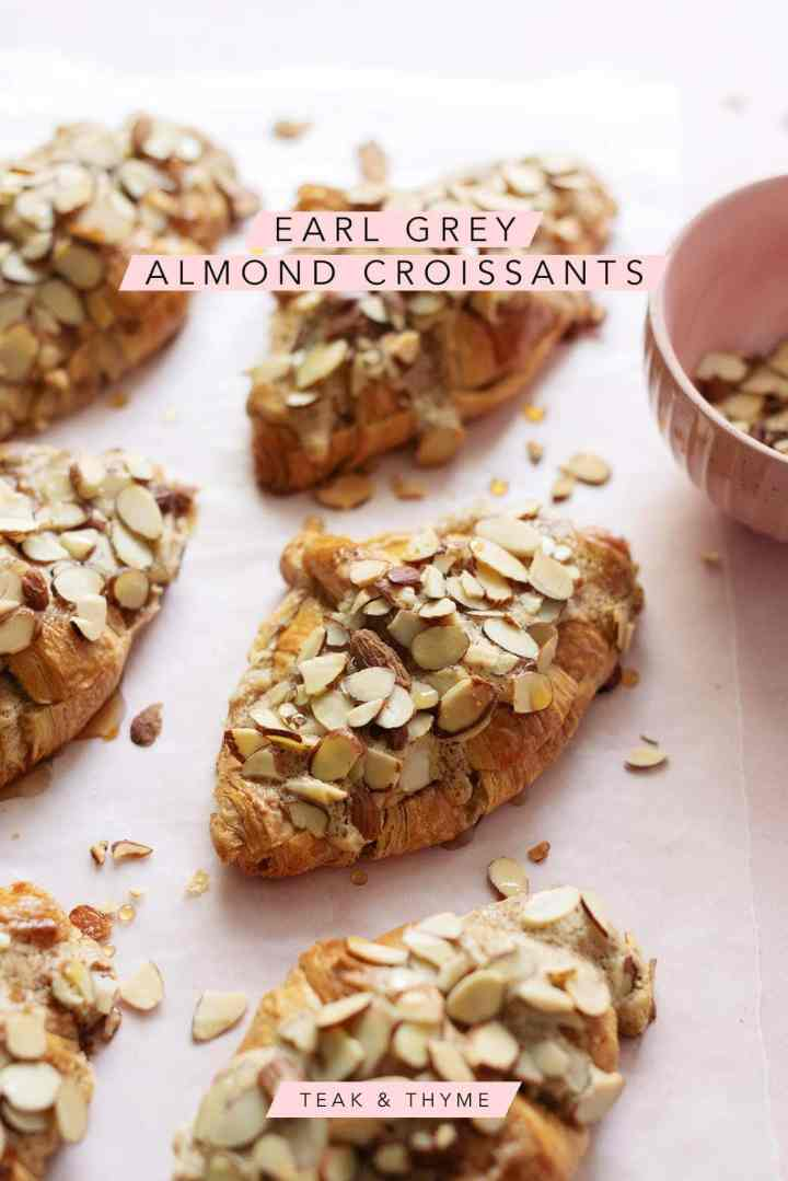 Almond croissants sprinkled with sliced almonds on pink background with text overlay