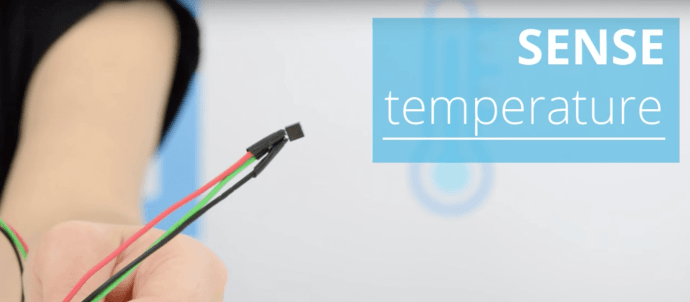 Hand holding a temperature sensor for iot
