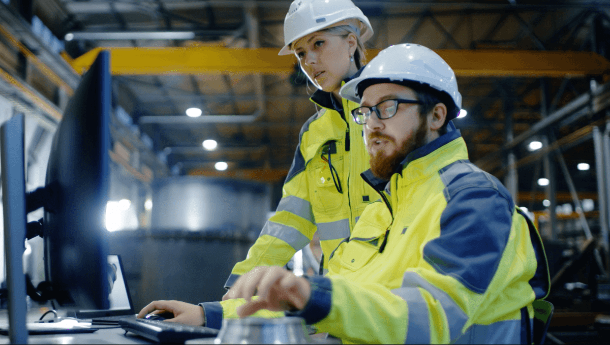 Two people in construction clothing looking at a computer in a warehouse