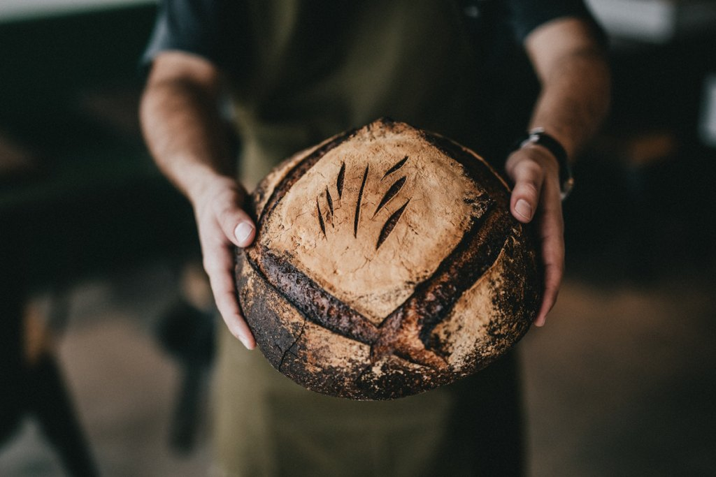 Bread baker holding a loaf of bread