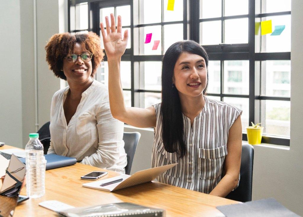 Two women – one woman raising her hand