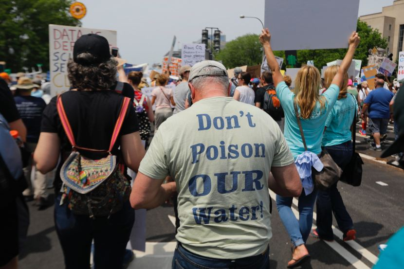 "Protester wearing a shirt that reads> ""Don't Poison OUR Water!"""
