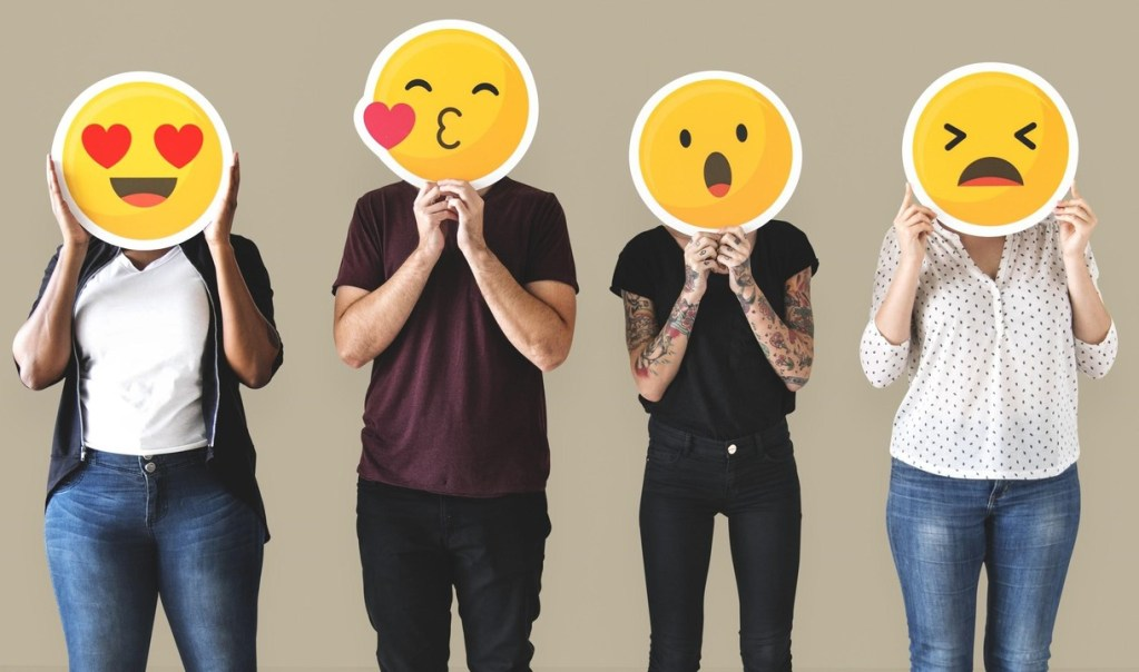 People holding up emojis over their faces