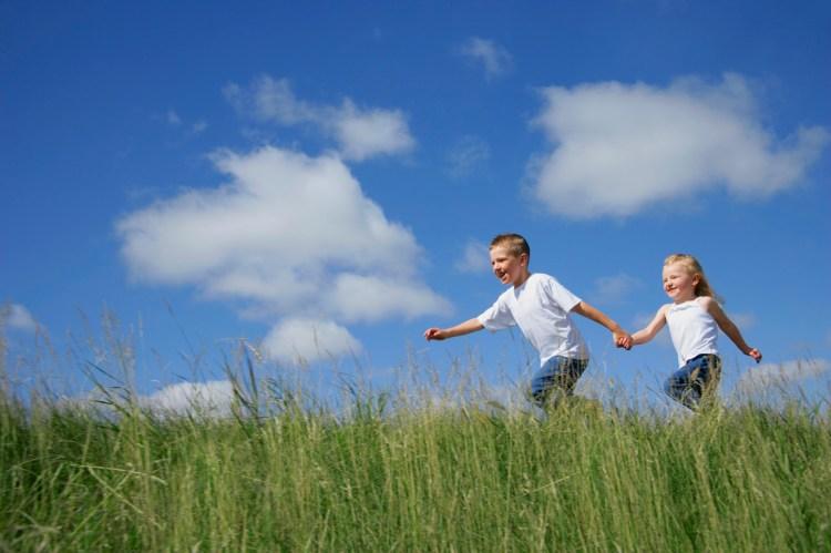 Boy and Girl Running in Tall Grass