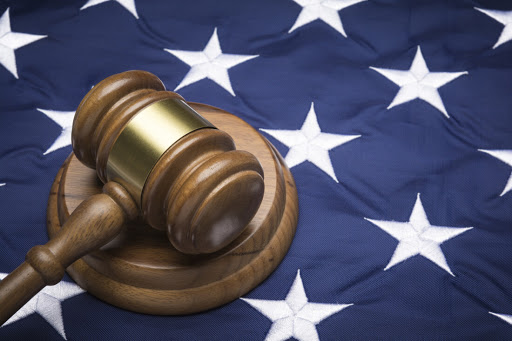 Judge's gavel over the stars of an American flag