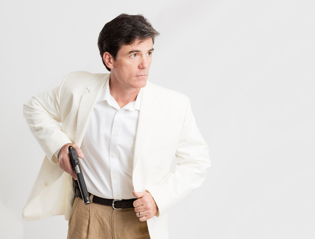 Man drawing a pistol of under his suit jacket dispelling self-defense gun control myths