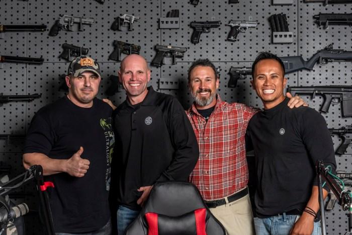 John Bartolo, Max Michele, Doug Koenig, JJ Racaza standing in front of the John Bartolo Show gun wall