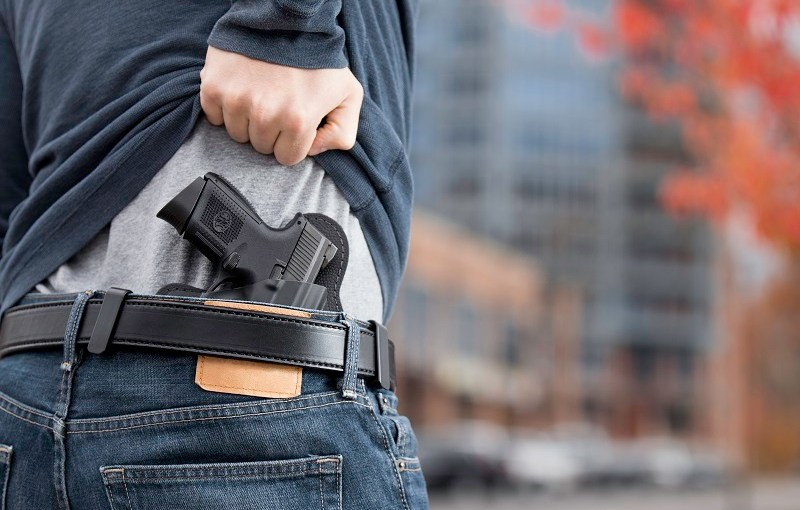 man lifting his shirt to expose a concealed pistol for constitutional carry