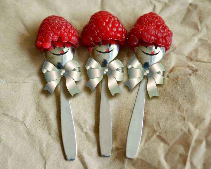 Spoons with happy faces and bows wearing raspberries for hats.