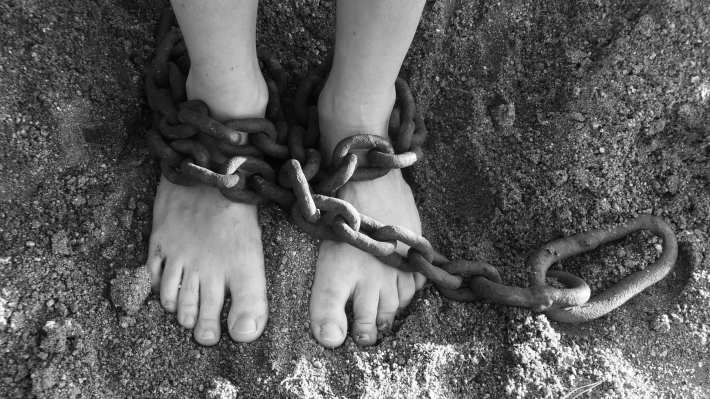 A black-and-white photo of feet, chained at the ankles.