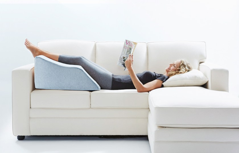 A woman is seen laying on a couch reading a magazine with her legs propped up on Lounge Doctor's elevating leg rest