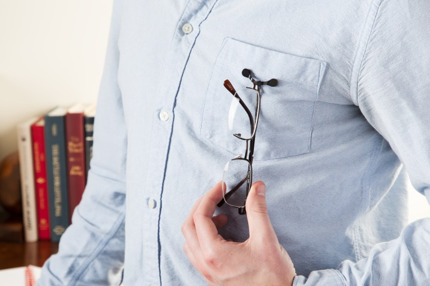A pair of glasses is seen clipped to a man's shirt pocket with a ReadeREST eyeglasses holder