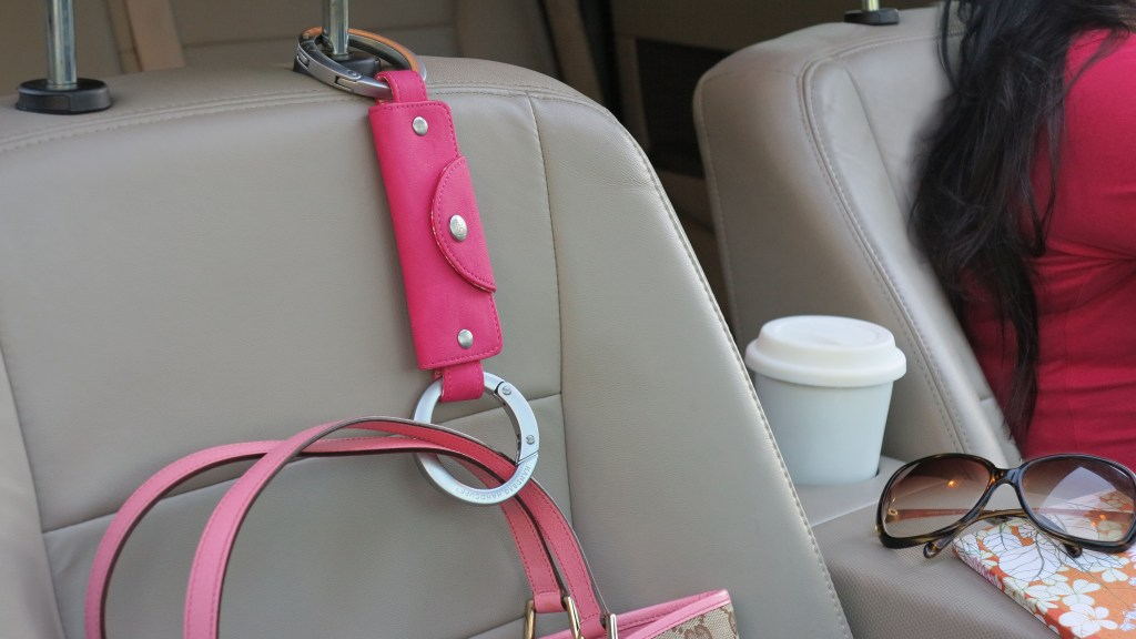 A pink Handbag Handcuff is seen clipped to a car headrest holding up a purse