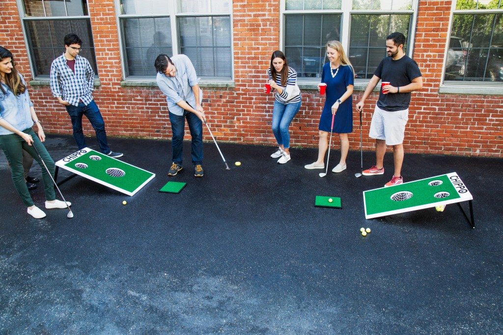 A group of friends playing Chippo Golf in their driveway