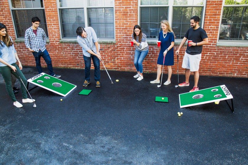 A group of friends plays Chippo outdoor golf game in their driveway