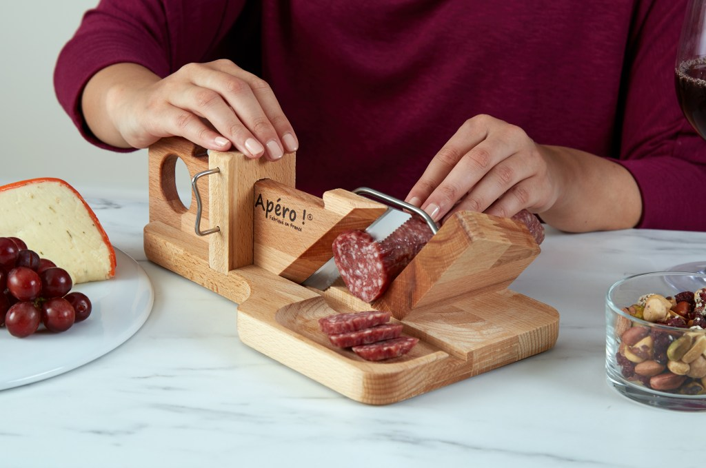 A person is seen using a So Apéro sausage guillotine to slice cured sausage