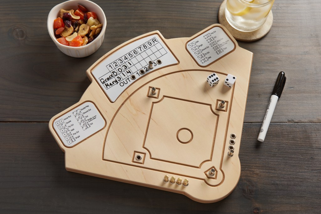 Across the Board wooden tabletop baseball game sits on a table with snacks