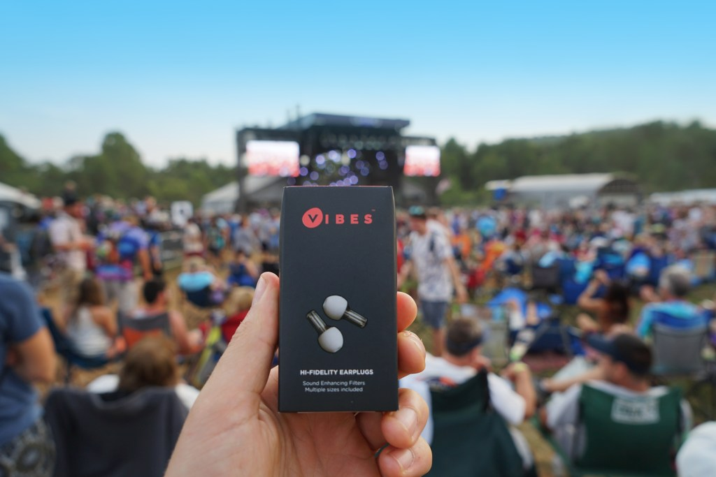 A box of Vibes hi-fidelity ear plugs is seen held up in a crowd at an outdoor concert