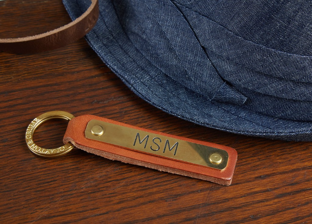 A leather key fob engraved with initials MSM on a nameplate from Clayton & Crume sits on a table