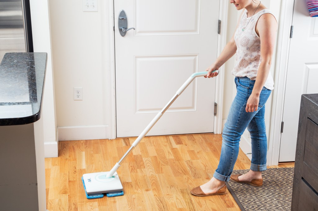 A woman uses Nellie's WOW Mop to wash her hardwood floors