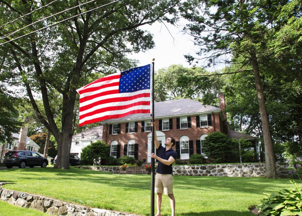 A man hangs an American flag in his yard with ease thanks to Flagpole Farm's titan telescoping flagpole