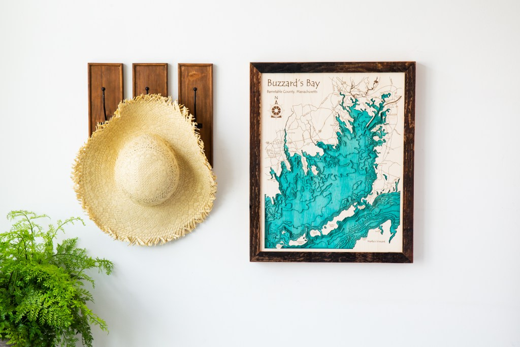 A custom lake art map of Buzzard's Bay hangs on a wall