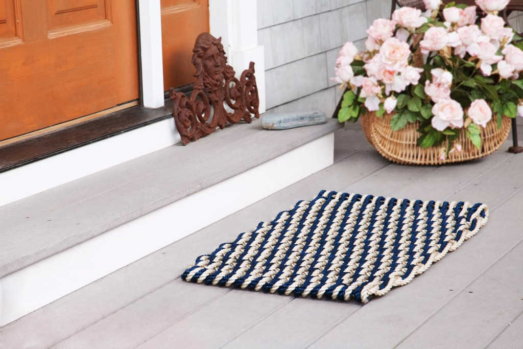 A blue & white nautical rope door mat from The Rope Co. sits on a front porch