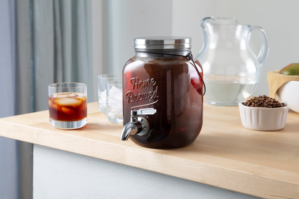 A glass jug of cold brew coffee sits on a counter, being pour from Willow & Everett's Cold Brew On Tap 2.0