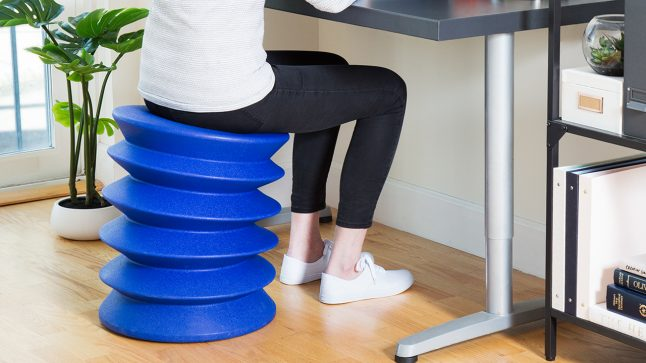 A woman sits on a blue Ergo Ergo while working at a desk