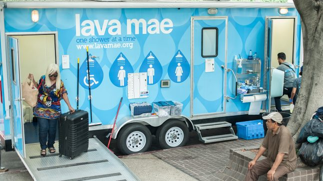 People are seen entering and exiting a Lava Mae portable shower bus.
