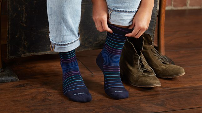 A person is seen putting on a pair of blue striped compression socks from Sockwell