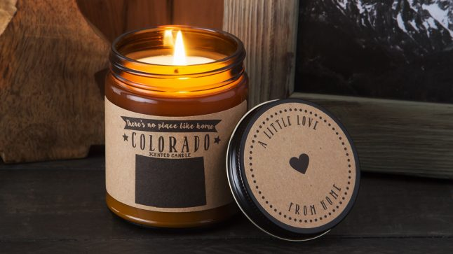 A Colorado state scented candle form no Place Like Home Candles burns on a mantle
