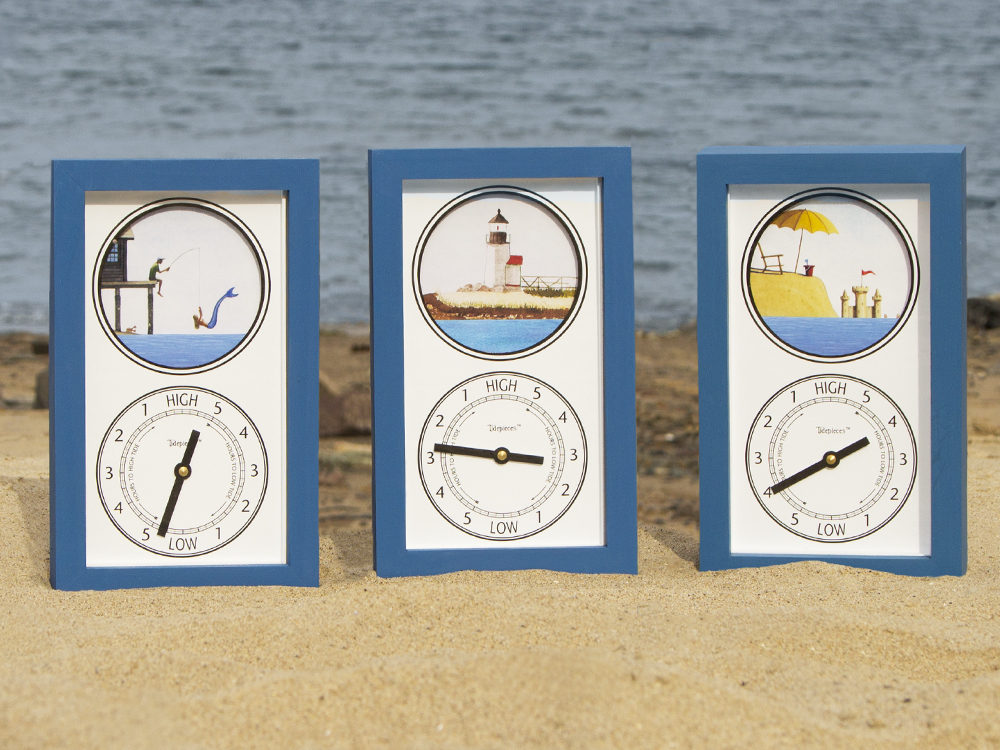 Timepieces' tide clocks depicting ocean scenes sit on a beach