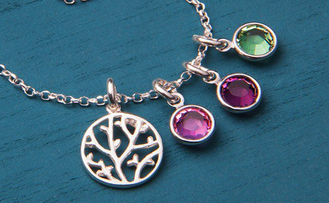 A family tree necklace with three charmed from Vintage Stamp Jewelry lays on a blue backdrop