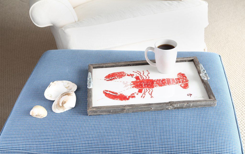A lobster-rubbed driftwood tray from Fish Aye trading sits on a blue ottoman