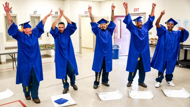 5 men in blue graduation cpas & gowns are seen celebrating having graduated from Defy Ventures' entrepreneurship training
