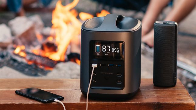 A person charges their phone by the fire with EcoFlow Tech's portable power station