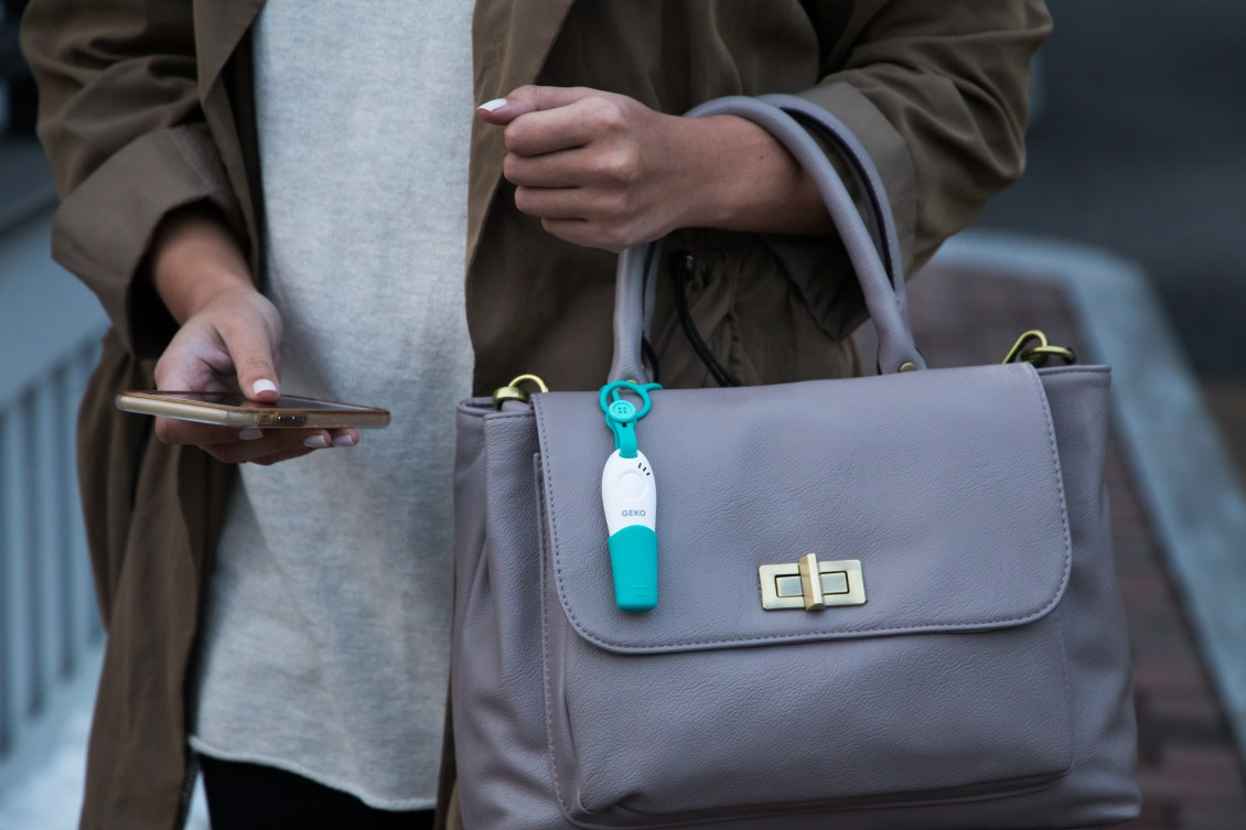 A teal & white GEKO safety whistle is strapped to a woman's purse