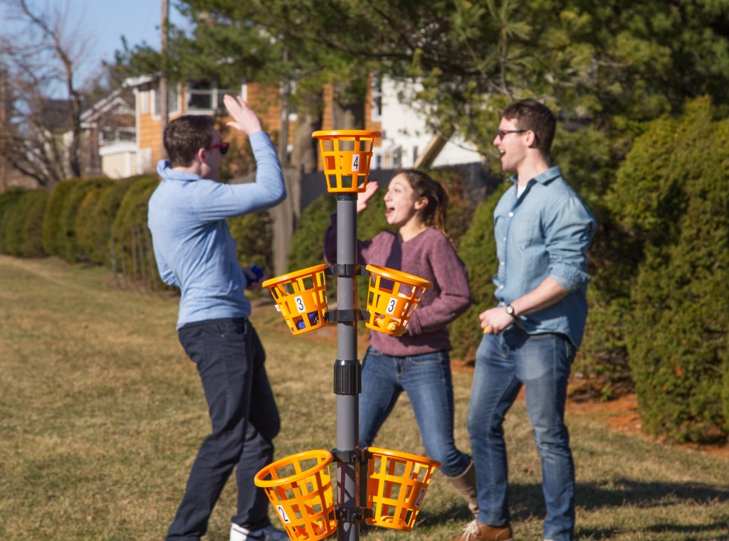 Three people play Bean Bag Bucketz' bean bag basket game in a yard