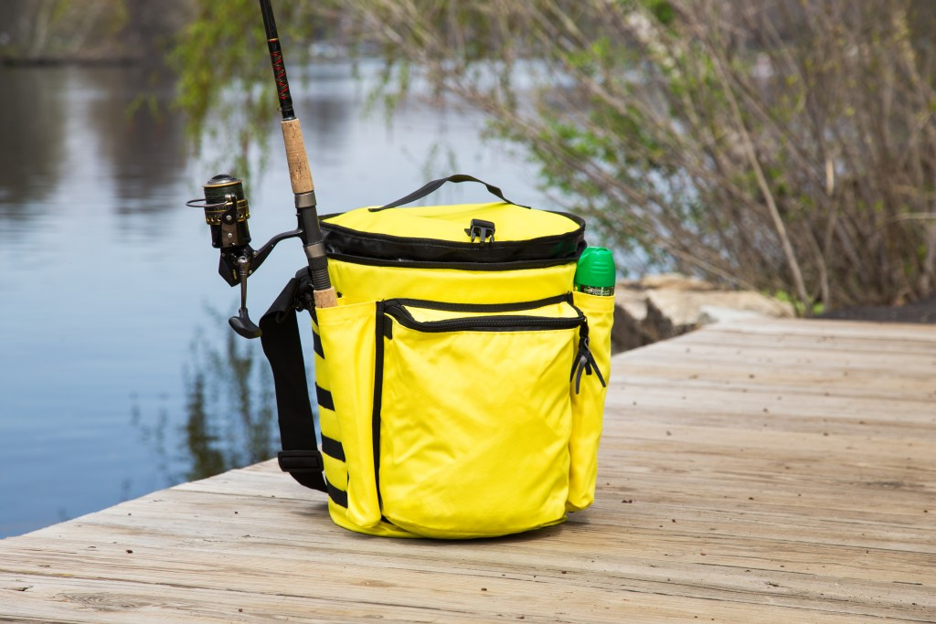 A yellow Boozie Bucket insulated cooler sits on a dock with a fishing rod and bug spray