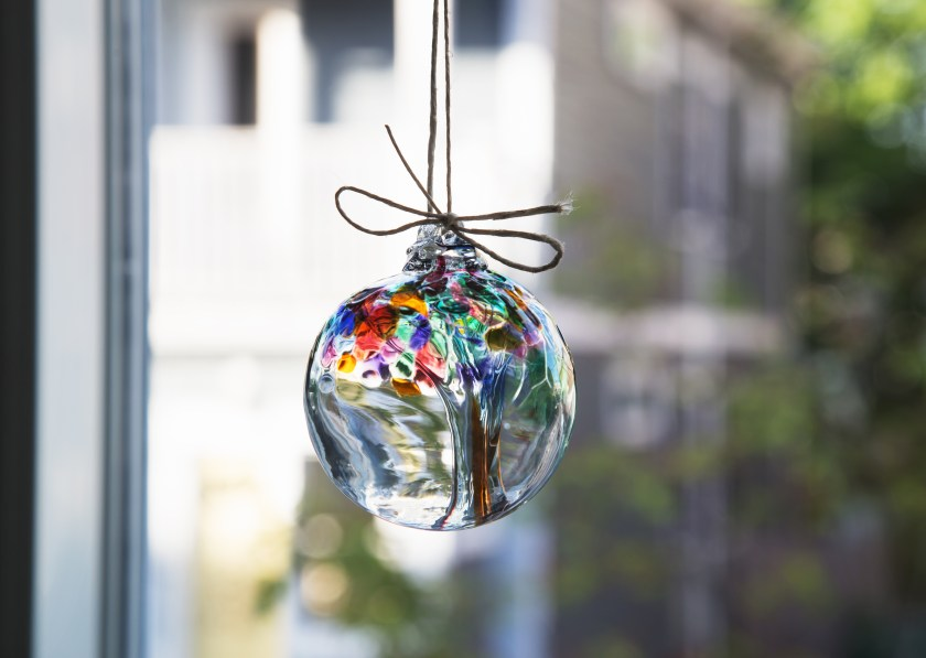 A tree of life hand-blown glass ornament from Kitras Art Glass hangs in a window