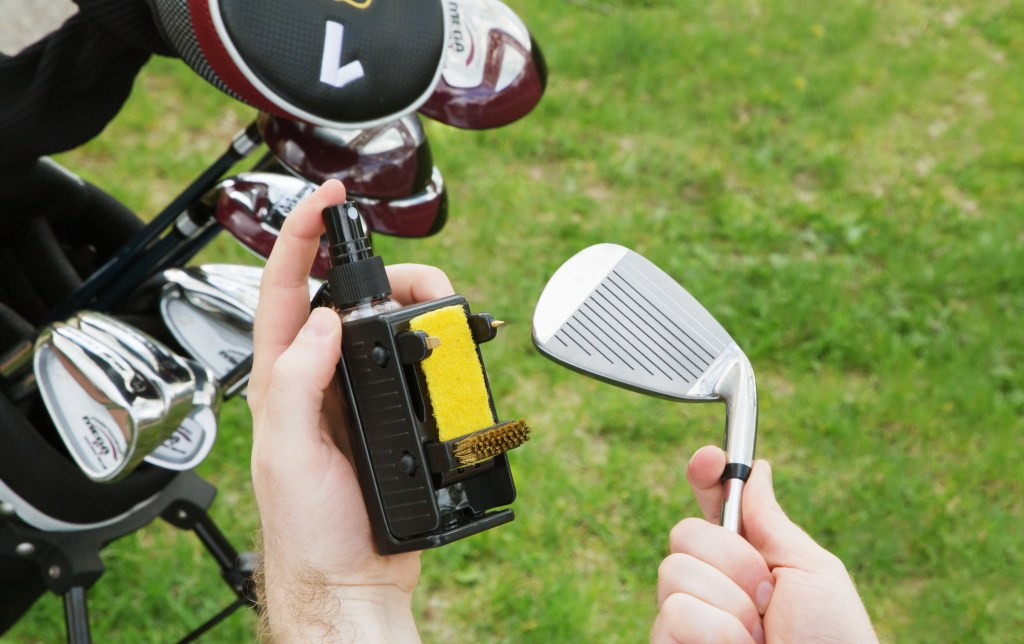 A person sprays Caddy-Clean golf club cleaner on their golf club