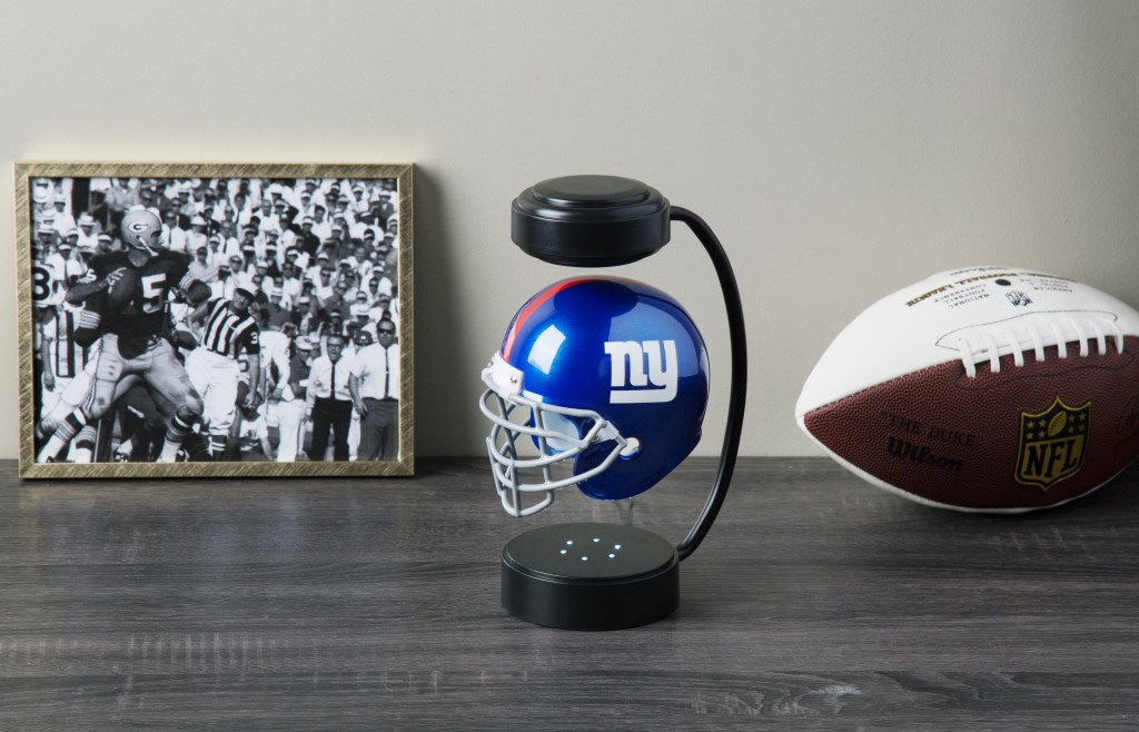 A New York Giants Hover Helmet sits on a desk with a football and a art print